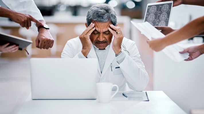 Physician burnout, doctor with hands on this head looking down at a desk